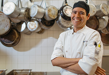 Culinary, Pastry and Hospitality student in front of pots and pans stand